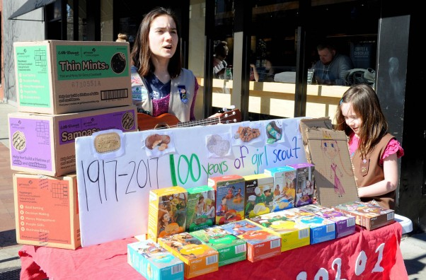 """Molly Sheridan (C) age 13, sings with her ukulele as she and her sister Edie age 5, sell Girl Scout cookies in Chicago on February 19, 2017. On a sunny Sunday afternoon, Molly Sheridan is hard at work in front of a Starbucks coffee shop in Chicago. The 13-year-old is playing her ukulele and, along with her five-year-old sister Edie, singing about Girl Scout cookies -- boxes of which she has arranged for sale on a table. """"Singing with my ukulele, I think that brings in people,"""" Molly says. It is Girl Scout cookie season, a uniquely American tradition marking its 100th year.   / AFP / Nova SAFO        (Photo credit should read NOVA SAFO/AFP/Getty Images)"""